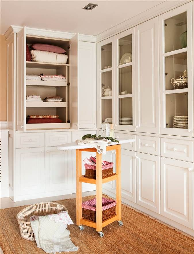 Planchador en blanco con armarios para guardar la ropa y tabla de planchar