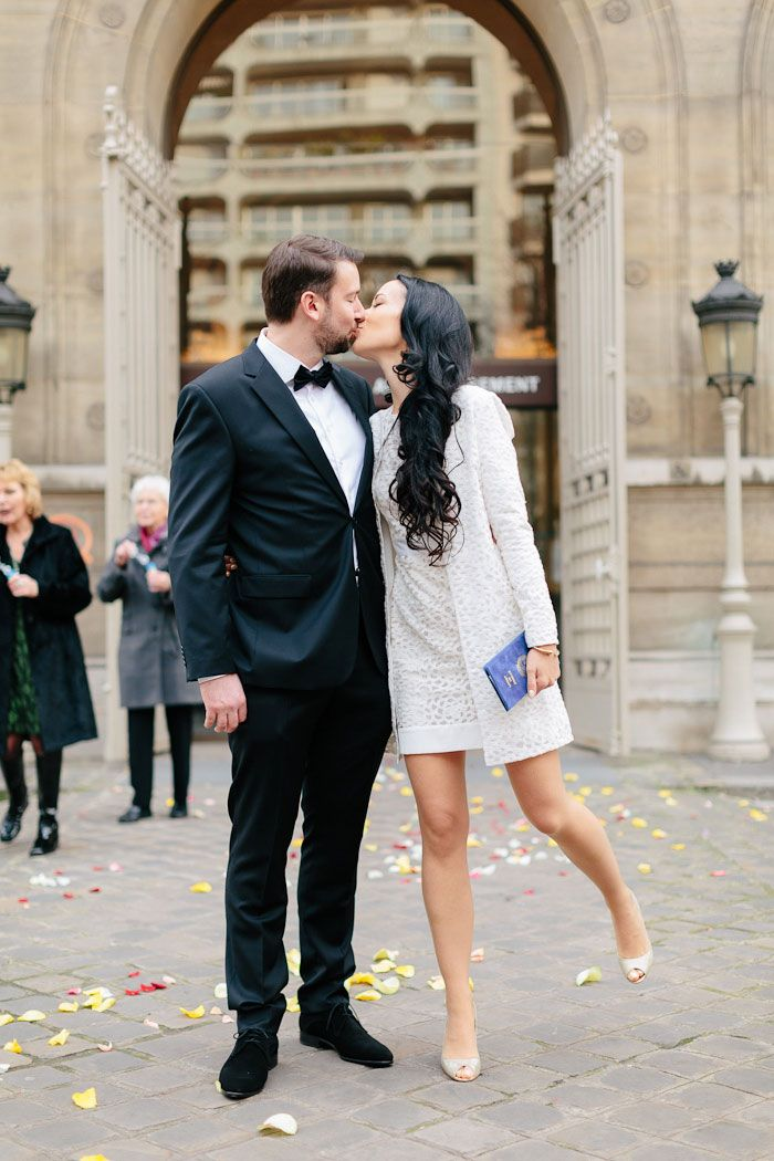 Love the matching coat. Bride and groom kissing in front of city hall.