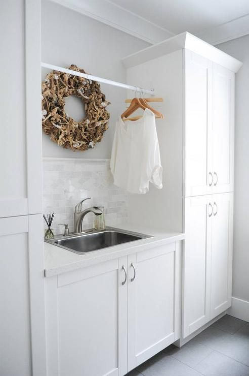 White and gray laundry room features a stainless steel sink under tension rod drying rack flanke dby tall white cabinets.