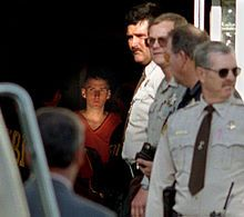 McVeigh is located at the center of the image in a dark hallway wearing an orange jumpsuit and looking to the side. Around him are several F...