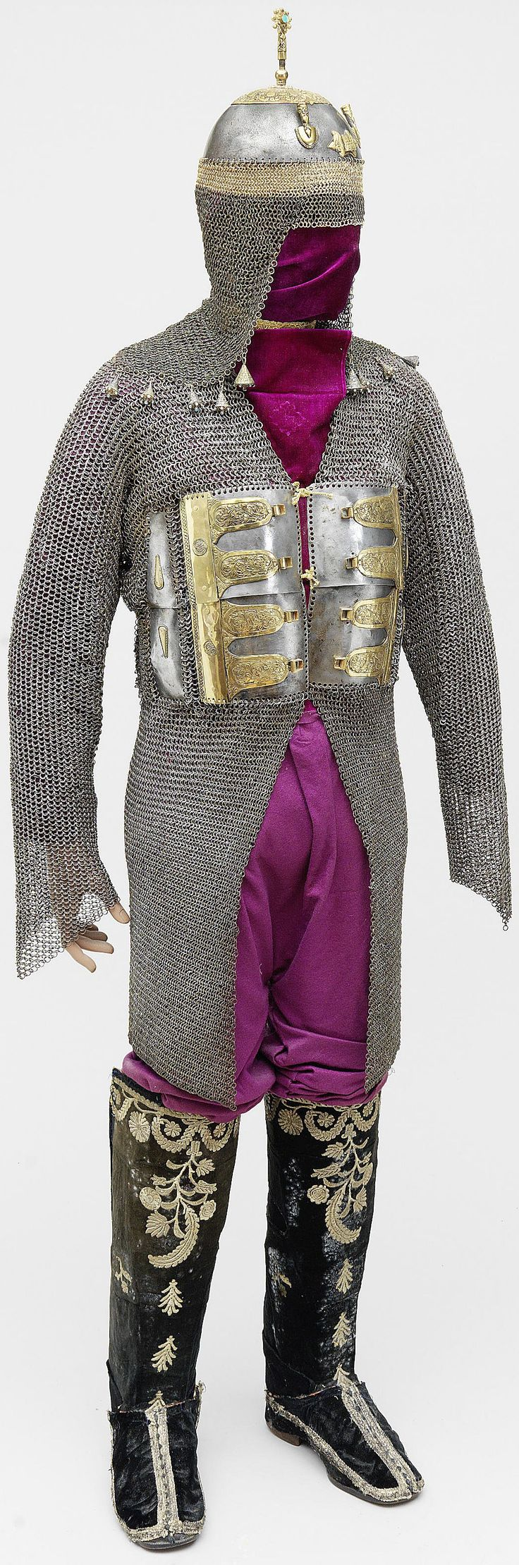 Indian (Deccan) zirah baktar (mail and plate armour shirt) 100 cm long, 17th Century, a long-sleeved mail shirt with seven frontal plates embellished with gilt mounts and four small inscription medallions, the back with five vertical rows of miniature plaques, khula-khud (helmet) and a pair of Ottoman 19th century embroidered velvet boots.
