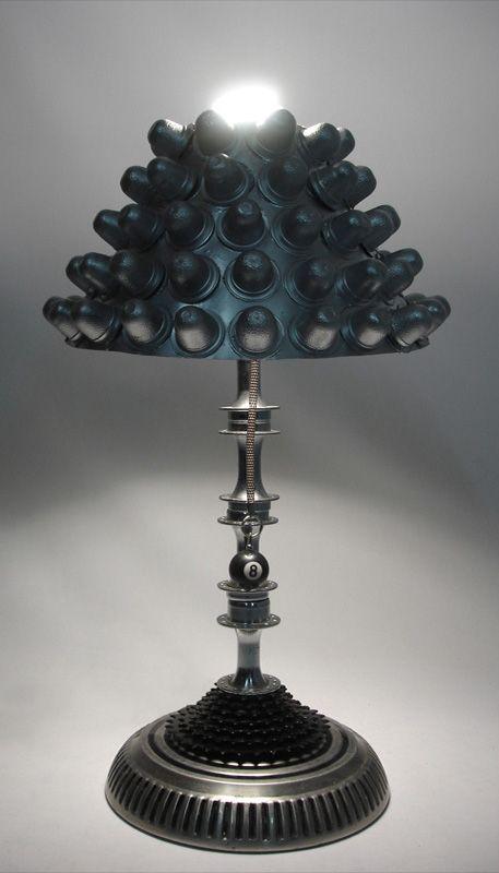 """Lámpara de mesa """"Metallica two""""   Materiales: tapón de carro, foco ahorrador de energía, 80 envolturas de golosinas, 4 ejes y 1 estrellas de bicicleta"""