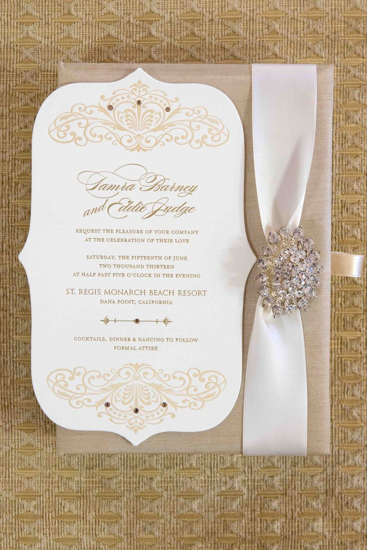 Tamra Barney and Eddie Judge's wedding invitation featured golden details and was displayed in a champagne-hued box fastened with a white ribbon and crystal brooch. #weddinginvitation #weddingstationery Photography: Christine Bentley Photography. Read More: http://www.insideweddings.com/weddings/tamra-barney-and-edward-judge/471/
