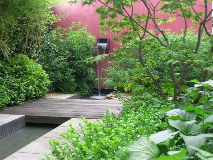 Bright focal point pink wall refreshingly contrasts with different shades of greenery while the wooden 'bridge' contrasts with the concrete paving/