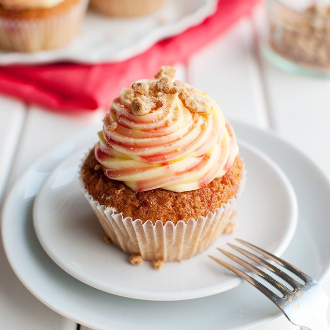 Rhubarb and Custard Cupcakes - These delicious cupcakes are filled with rhubarb puree and topped with a swirl of custard buttercream, rhubarb syrup, and crunchy crumb topping. Yum!   thetoughcookie.com