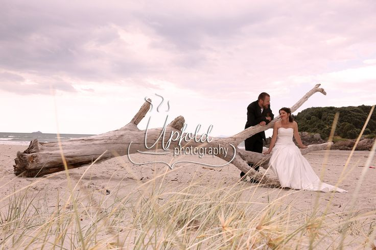 Elegant bride and groom seated on a long piece of driftwood, giving a sense of endlessness - a great symbol of their marriage ahead of them. Image by Upfold Photography. ~ wedding in Tauranga ~ beach wedding photos ~ bride and groom together ~ driftwood tree ~ elegant and rustic combined ~