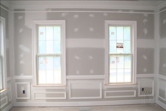 """This shows a Living room with a 5 piece crown moulding, 2 piece chair rail, panel moulding shadowboxes, 5"""" baseboard, and windows with a 3.5"""" Adams casing."""