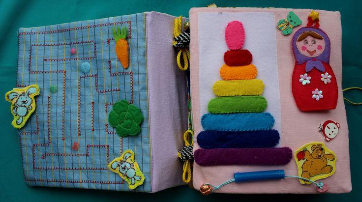 Первая страничка- лабиринт. Все детали съемные.Вторая- перетяжка, пирамидка по цветам радуги на липучке, в матрешке прячутся еще 3 маленькие матрешки.