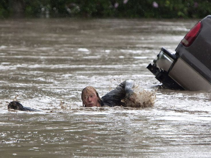 Kevan Yeats swims after his cat Momo to safety as the flood waters sweep him downstream and submerge the cab in High River, Alberta on June 20, 2013 after the Highwood River overflowed its banks. Hundreds of people have been evacuated with volunteers and emergency crews helping to aid stranded residents.