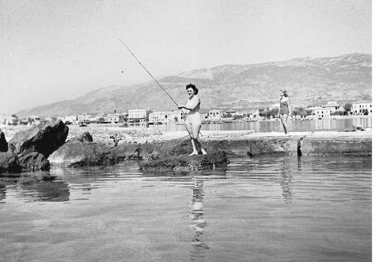 """Κοπέλα με μαγιό ψαρεύει στον κυματοθραύστη, δεκαετία 1940-1950.  Στο βάθος διακρίνεται το σύνολο των κτηρίων της Ναυαρίνου στο ύψος της προκυμαίας.  [Από το λεύκωμα των ΓΑΚ Μεσσηνίας Αν. Μηλίτση-Νίκα, Στ. Βερράρου """"Η Καλαμάτα μέσα από το φακό του Χρήστου Αλειφέρη 1937-1974"""" σελ. 127"""