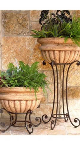 ~Tuscan-style garden urns on iron stands display Boston ferns. The fronds add…