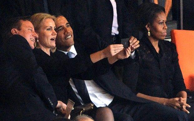 Michelle Obama looks away as (L-R) British Prime Minister David Cameron, Danish Prime Minister Helle Thorning-Schmidt and US President Barack Obama take a selfie
