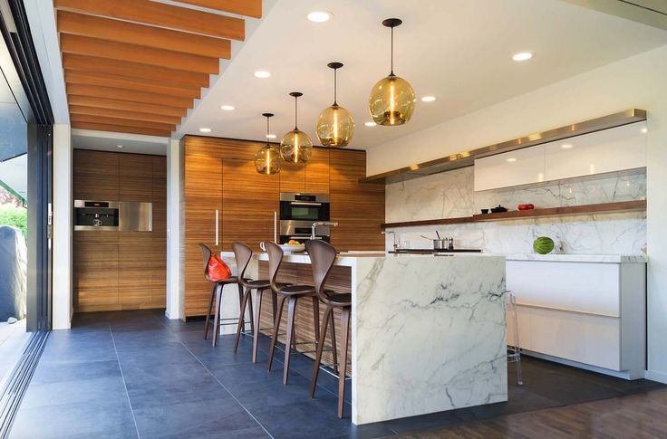 This mid-century modern kitchen blends easy to clean marble with warm wood tones for an inviting, contemporary space.