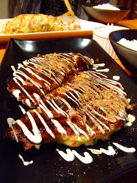 OkonomiyaKi, Japan; Very different to the Western style pancake, Okonomiyaki (translated as 'As-you-like-it pancake') is a savoury mix of egg, noodles and cabbage filled with all sorts of fillings from cheese and wasabi to seafood, pork and chicken. It's cooked on a griddle and typically served with a Japanese mayonnaise in zig zag lines and katsuobushi (smoked bonito) and aonori (seaweed) across the top.  http://www.virginholidays.co.uk/destinations/asia-&-far-east/japan-holidays