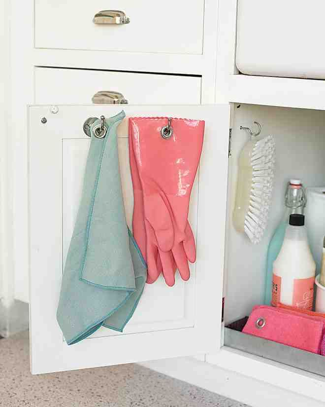 Don't let damp rags and dishwashing gloves clutter the sink area. Instead, hang them from hooks screwed to the inside of a cabinet door, where the items can stay hidden as they dry.