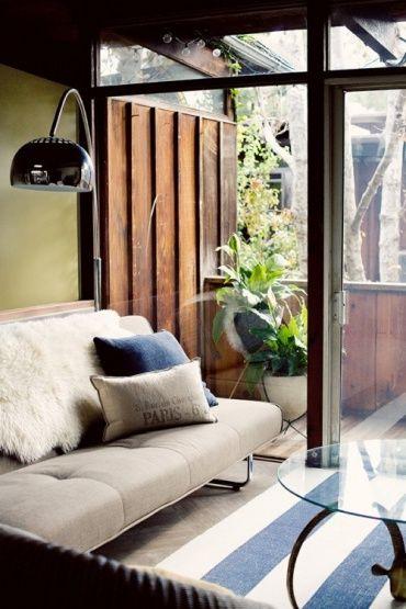 壁は黄緑の土壁のような色で、白と水色のストライプのマットとベージュのソファがあるリビングです。掃き出し窓の向こうは、古民家風の板でできたベランダです。