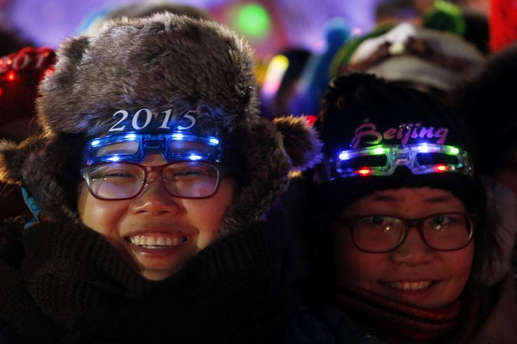 """Women wear eyewear in the shape of the year 2015 as they wait for a countdown event to celebrate the arrival of the new year and in wishing winning the bid to host the 2022 Winter Olympic Games, in front of the National Stadium, also known as the """"Bird's Nest"""", in Beijing, Dec. 31, 2014.   Photo by Kim Kyung Hoon/Reuters"""