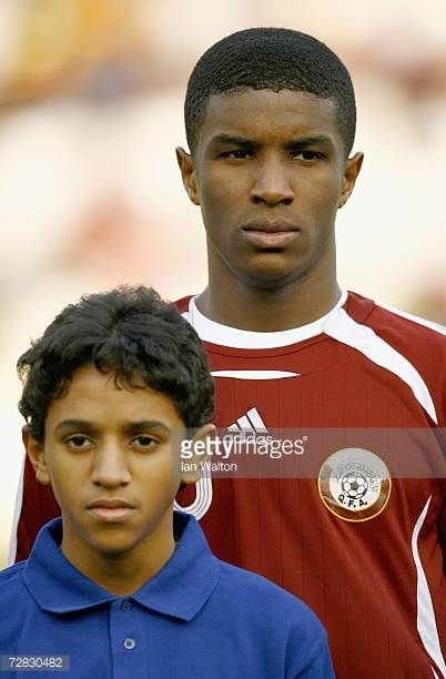 Bilal Mohammed Rajab of Qatar stands for the national anthem during the gold medal match between Qatar and Iraq at the 15th Asian Games Doha 2006 at...