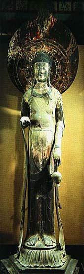 世界文化遺産 法隆寺地域の仏教建造物 国宝百済観音像は、飛鳥時代を代表する仏像で、広隆寺所蔵の弥勒菩薩像などと ともに、昭和26年に初めて国宝に認定された作品の一つです。  像の高さ2.09m、八頭身の長身で、樟の一本造りで両腕の肘からさきと水瓶 、天衣など別材を継いで造っています。宝冠は線彫りの銅版製で三個の青いガラス玉で飾られています。独特の体躯の造形を有し、杏仁形(アーモンド形)の目や古式な微笑みをたたえる表情は神秘的であり、多数の随筆等によって紹介されるなど、我が国の国宝を代表する仏像の一つです。  本来、百済観音は、虚空像菩薩として伝わっていました。虚空とは、宇宙を意味し虚空菩薩は宇宙を蔵にするほど富をもたらす仏様ということなのです。 その宇宙の姿を人の形に表したのが百済観音だというわけです。