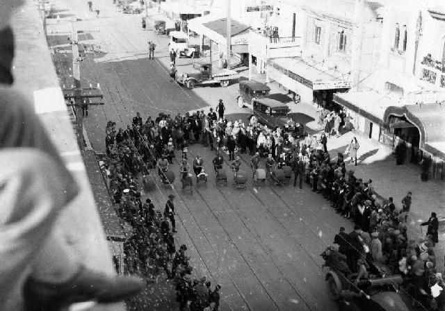 New Napier Week Carnival  The photograph shows women pushing prams in a race along Dickens Street, Napier. The celebrations were part of the New Napier Week Carnival. These were held in early January 1933, to celebrate the rebuilding of Napier after the 3 February 1931 earthquake. The tram lines can be seen embedded in the road.  Photographer, Dave Williams. Date, January 1933.
