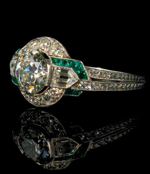 Circa 1925 an Art Deco ring by Tiffany & Co. featuring emeralds and diamonds set in platinum.