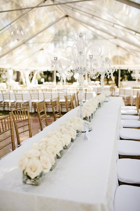 Elegant white. Low table arrangements are always a classy choice. You can save $ by using inexpensive containers, rather than bigger, dramatic centerpieces.