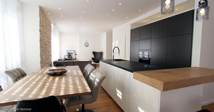 Die Küche mit den dunklen Hochschränken, integrietr sich harmonisch in das Gesamtbild. Die Kochinsel wurde zum Kontrast in weiß gestaltet. Geräte wurden in schwarz gehalten um in den Hintergrund zu treten