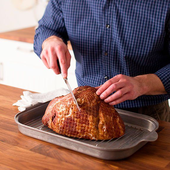 person scoring a ham with a knife in a diamond formation