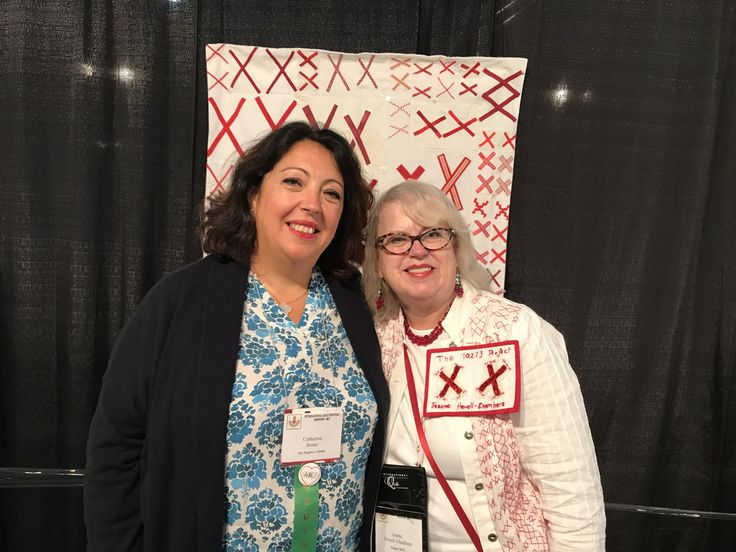 L to R: Catherine Bonte (President of the France Patchwork Guild) and Jeanne Hewell-Chambers (Founder of The 70273 Project) standing in front of a quilt made in France for The 70273 Project