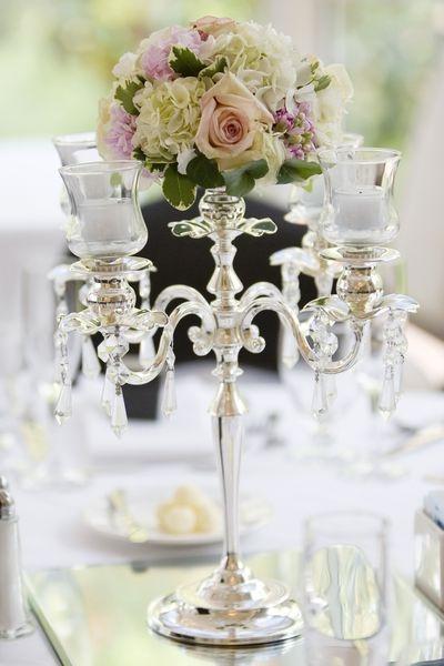 Schöner Kerzenständer mit weißen Kerzen und integriertem Blumengesteck.