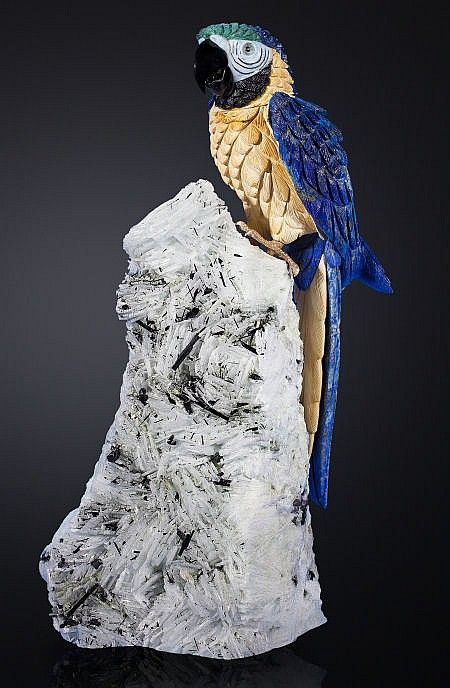 BLUE MACAW IN LAPIS ON ALBITE, MICA AND TOURMALINE BASE Artist: Peter Müller Stone Source: Brazil   This large, majestic Macaw sits perched in a truly lifelike position on its exquisite mineral base. Looking as though it is about to call out, this lovely bird features wings fashioned in regal blue Lapis with intricate detailing throughout. Contrasting the striking azure blue of the wings is a sublime buttery yellow Mookaite breastplate which follows down through the inner feathering of the…
