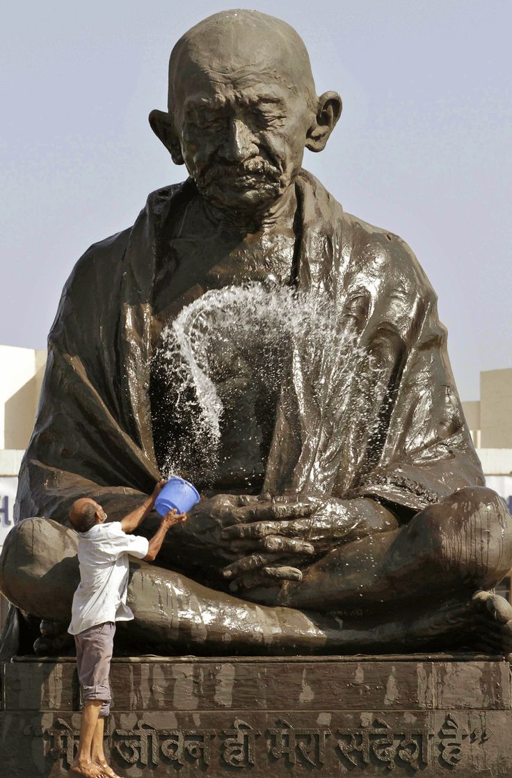 A man throws water on a statue of Mahatma Gandhi as he cleans it on the eve of Gandhi's birthday at the Gujarat state legislature complex in Gandhinagar, India, on Oct. 1, 2012. Gandhi was born on Oct. 2, 1869.   (Photo: Ajit Solanki / AP)