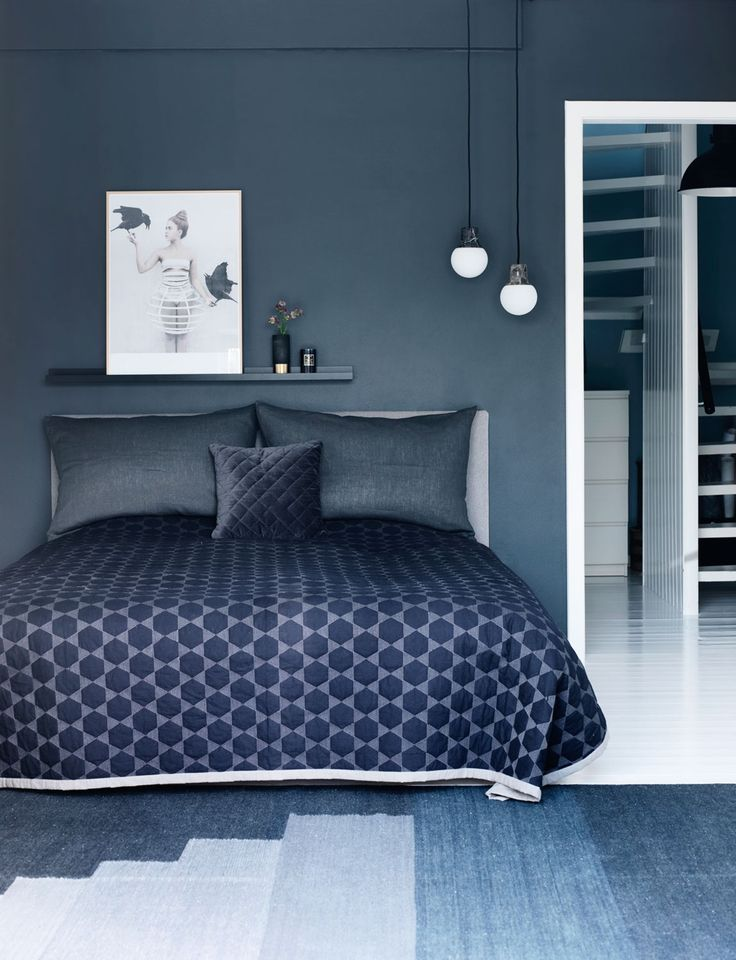 Blått soverom med blått sengeteppe, puter og gulvteppe.