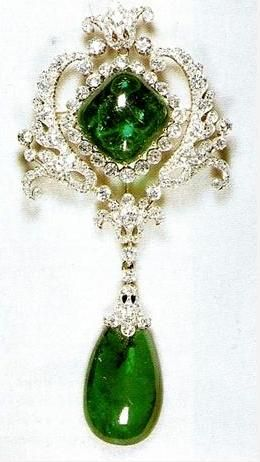 The Scroll Cambridge Emerald Brooch, part of the Personal Jewel Collection of Queen Elizabeth II. It is composed of platinum and diamonds, and features two of the Cambridge Emeralds. The brooch and its drop were originally crafted in 1911 as part of the Delhi Durbar Stomacher, but can be detached and worn separately.