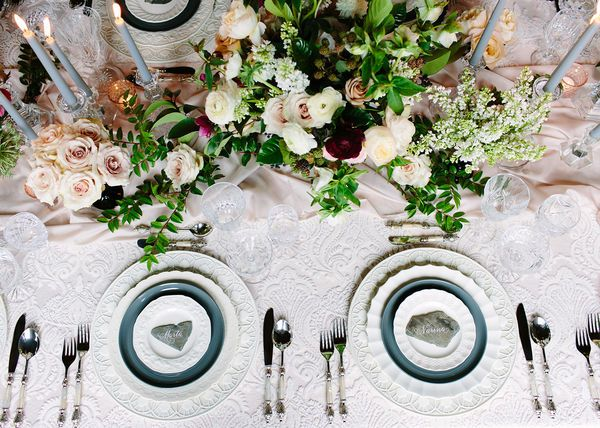 Calligraphy and slate seating cards on a beautiful classic wedding table with flower arrangements and gray taper candles.