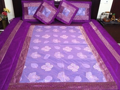 Purple coloured bed cover set from Zafraan. Made of pure silk and tissue, this 5-piece set comprises of 1 bed cover, 2 pillow covers and 2 cushion covers.
