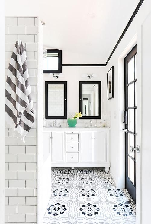 Fantastic bathroom boasts a white dual washstand under his and hers black framed medicine cabinets fitted with mirrors alongside a black and gray Moroccan tile floor.