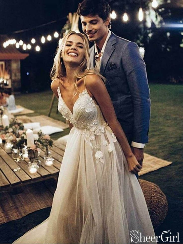 This wedding dress features lace applique over the ruched top. Featuring a v-nec…