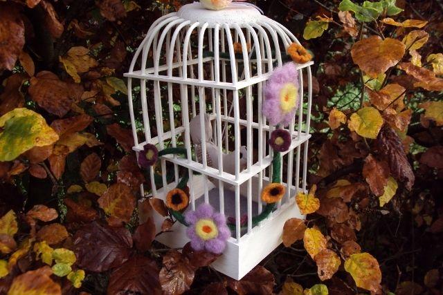 Oui, sauf que celle-ci (achetée l'année dernière à Brico Marché) n'a pas de porte. J'ai dû glisser l'oiseau entre les barreaux. Je l'ai peinte car elle était en bois brut. J'ai réalisé la guirlande de fleurs en laine feutrée à la main (eau et savon) et...