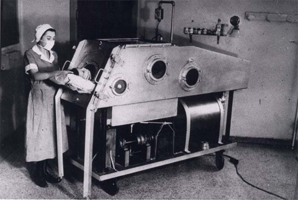 """Nurse with child in """"Iron Lung"""" constructed at The Hospital for Sick Children, Toronto, Canada, during 1937 polio epidemic (The Hospital for Sick Children Archives, Toronto, Canada)"""