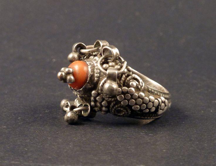 Vecchio anello di Yemen, fatto con una perlina di corallo e argento. Argento di alta qualità, riccamente decorata con filigrana. Alcune piccole dangles argento appendere su ogni lato dellanello. Tutto lanello ha una patina di vecchia e logoro.  Alcuni di questi anelli da Yemen erano molto molto apprezzati dal popolo Rashaïda dellAfrica orientale.  Dalla fine del 19 ° o inizio XX secolo.  La dimensione dellanello è 7 1/2 (americano) o 16 (europea). (YEM81)  Spedizione da DHL.    Per torna...