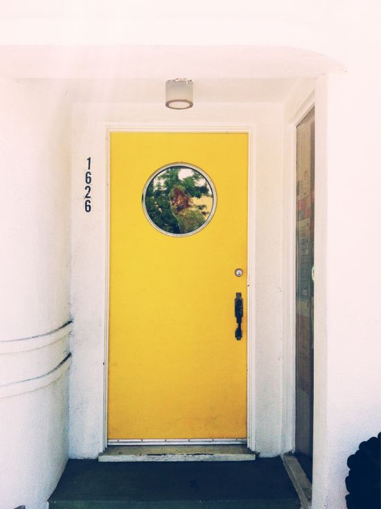 Yellow door with porthole window.