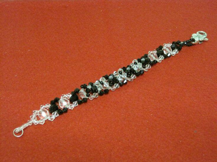 Bracciale a doppia lavorazione con cristalli neri e trasparenti con finizioni floreali Swarovski neri e trasparenti. Chiusura con moschettone floreale argentato.
