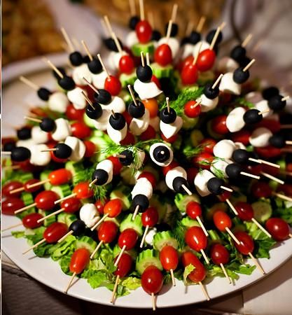 Great veggie kabob presentation! Tomatoes, olives, mozzarella and cucumber skewers inserted into a half a head of lettuce.