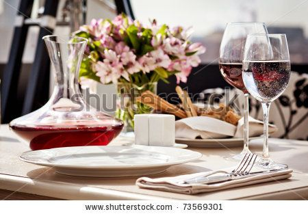 Fine restaurant dinner table place setting: napkin, wineglass, plate, bread and flowers - stock photo