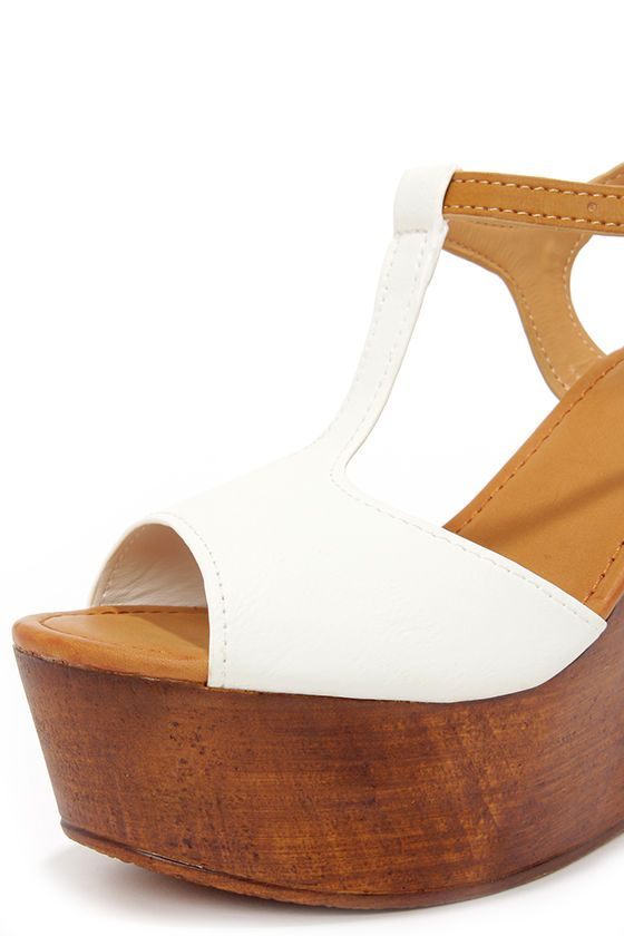 """A day at the boardwalk deserves all the cotton candy you can eat, and a spin in the Fairest Wheel White Wedge Sandals! Smooth white vegan leather kicks off a peep toe, T-strap upper, with an adjustable tan quarter strap (and gold buckle). Lightweight wood-look platform wedge measures 4.75"""" at the heel, and 1.75"""" at the toe. Lightly cushioned insole. Textured synthetic sole. Available in whole and half sizes. Measurements are for a size 6. All vegan friendly, man made materials."""
