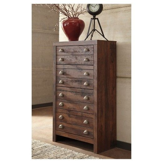 Take a minimalist chic profile. Merge with a rustic aesthetic. Add a touch of industrial cool. If that's your style, this apothecary-inspired chest of drawers might be the perfect fit. Four smooth-gliding drawers—adorned with classic cup pull hardware—are packed with possibilities. Cognac-colored finish over replicated cherry grain is something to savor. Signature Design by Ashley is a registered trademark of Ashley Furniture Industries, Inc.