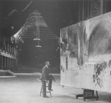 "Tom Roberts working on ""The Big Picture"", his epic painting of the opening of the first parliament of Australia, at the Royal Exhibition Building in Melbourne."