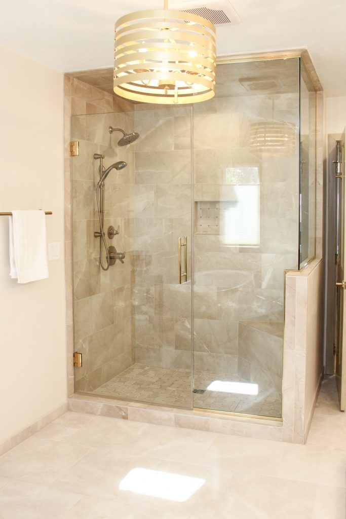 Beige Marble Tile Shower With Glass Shower Door And Gold Accents