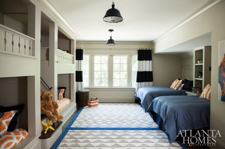 Grandchildren frequent the spacious bunk room, which was a fun and unexpected addition to the second floor, mirroring the blue and orange hues that anchor the home. Each pillow is monogrammed with a child's name.